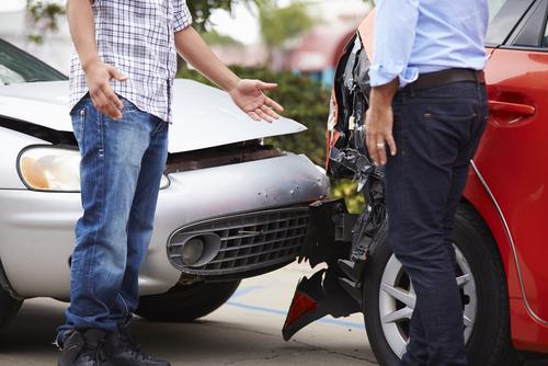 Two gentlemen exchanging information after a car crash